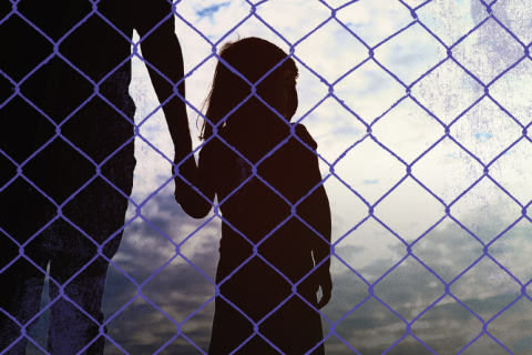 Girl behind chain link fence
